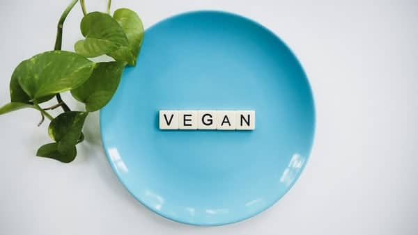 Blue Plate With VEGAN Spelled out in Scrabble Letters With a plant next to it on a white table and blue background